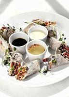 asian fresh vegetable vegan spring rolls with sauces on white restaurant table background in hanoi vietnam.