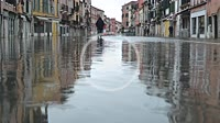 "People walking in Via Giuseppe Garibaldi, a major street in Castello Quarter, during during the so called """"acqua alta"""" high tide. Venezia. Italy."