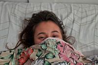 Girl scared in the bed with flowers bed sheets close up.