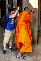 A Buddhist Monk Taking Photos, Angkor Wat, Siem Reap, Siem Reap Province, Cambodia.