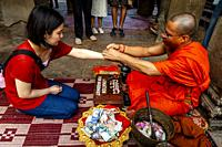 A Buddhist Monk Giving A Blessing, Angkor Wat, Siem Reap, Siem Reap Province, Cambodia.