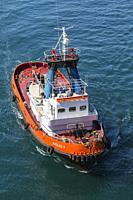 Top view of orange, red and white Nikolaos V tugboat, Piraeus port, Athens, Greece.
