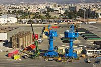 Dock with blue gantry cranes and chemical storage tanks, Limassol port, Cyprus.