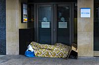 Homeless sleeping in front of bank branch. View of a street of Chamberi quarter. Madrid city, Spain. May, 2020
