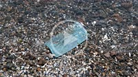 Wave washes off the face mask in the sea. Close-up of used disposable medical mask on the pebbles beach in surf zone. Coronavirus (COVID-19) is contri...