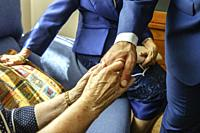 The groom holds his grandmother´s hands lovingly on the wedding day