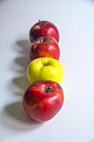 Three red apples and a green one in a row.