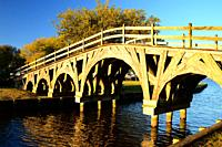 A beautiful wooden pedestrian bridge crosses a small creek in a park in the Outer Banks of North Carolina.