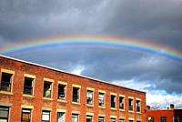 A rainbow appears over an old, repurposed industrial building in Keene, New Hampshire.