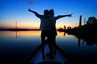 Two Women raising their arms in cross sign of happiness and freedom in the stern of a boat in the Albufera of Valencia, Spain