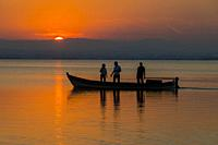 Silhouette of three people a boat in the Albufera de Valencia at the sunset, Spain