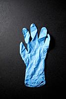 Latex glove on a black table.