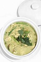 thai green curry with chicken and vegetables on white table background.