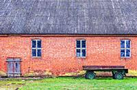 Country idyll with wrecked trailer in front of a dilapidated brick stable building, Mecklenburg-Pomerania, Germany.