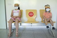 Children sitting on waiting chairs with social distancing sticker. Healthcare center hallway.
