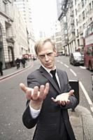 preternatural businessman with open hand palms at street in city of London, UK.