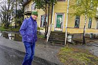 Arkosund, Sweden Pedestrians walking in the village near an old house.