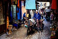 A man riding a donkey and cart through the medina in Marrakech, Morocco, North Africa.