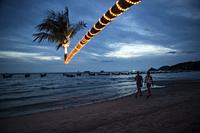 People having a walk at the shore of Sairee Beach at twilight, Koh Tao, Thailand.