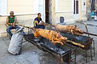 Roasting pigs in a pedestrian area of the town centre in order to subsequently sell meat portions to the public. Manzanillo, Cuba.