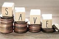 Stack of coins with save letter in wooden block, Time to Saving Concept growing money stairs close-up.
