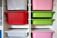 Stack of plastic storage boxes in different colors, sorting system arrangement close-up.