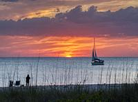 Sailboat in the Gulf of Mexico at sunset with an orange sky off Nokomis Beach ion the Gulf coast of Florida.