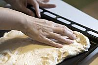 Pressing Pizza Dough Into Oven Tray. . .