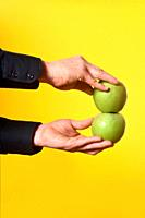 hand holding a two apple on yellow background.