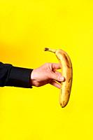 hand holding a banana on yellow background.