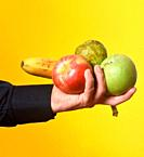 hand holding a group of a fruits on yellow background.