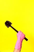 hand with glove hoding brush on yellow background.