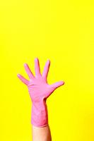 hand with glove, palm, on yellow background.