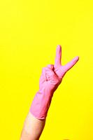 hand with glove and v sign on yellow background.