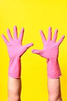 gloved hands raised on yellow background.