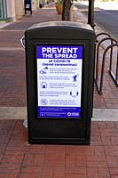 Prevent the Spread of Covid-19 sign on a sidewalk trash can in downtown Tucson AZ.