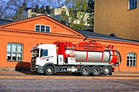 White Scania vacuum and pressure tank truck of J&J Puhallus Oy driving on street in city traffic in morning light. Helsinki, Finland. May 6, 2020.