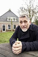 senior man in front of home in Friesland, Netherlands.