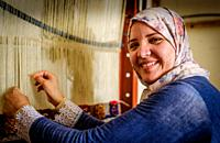 A young Berber woman weaving a carpet in Tazenakht, southern Morocco, North Africa.