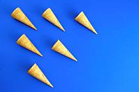 six of ice cream cone waffle in geometric formation on blue background. Concept. Copy space.