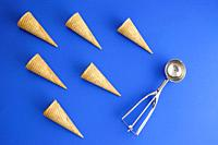 six of ice cream cone waffle in geometric formation and ice-cream spoon on blue background. Concept. Copy space.