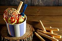 Two vanilla ice cream balls with sirope on ceramic bowl with blue plastic teaspoon and biscuit on wood slice and various biscuits on wooden background...