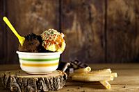 chocolate and vanila ice cream balls on ceramic bowl with yellow plastic teaspoon and biscuit on wood slice and various biscuits on wooden background....