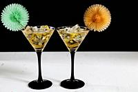 two cocktails glasses with green and orange ornaments on black and white background. Copy space.