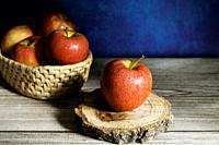 Delicious red apple on wood slice and apples group in basket on wooden table and abstract blue background.