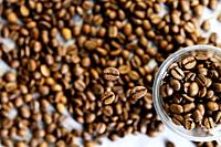 selective focus of coffee beans and coffee beans in a glass cup on unfocused background of coffee beans.