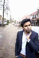 Indian businessman thinking in Leeuwarden, Friesland, Netherlands, Europe.