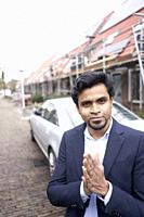 Indian business man feeling ready in front of newly constructed house and car in residential district in Leeuwarden, Friesland, Netherlands, Europe