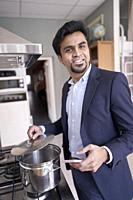 Indian business man cooking with smartphone in hand
