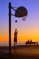 A man takes a jump shot at a court near the seashore in Laguna Beach.